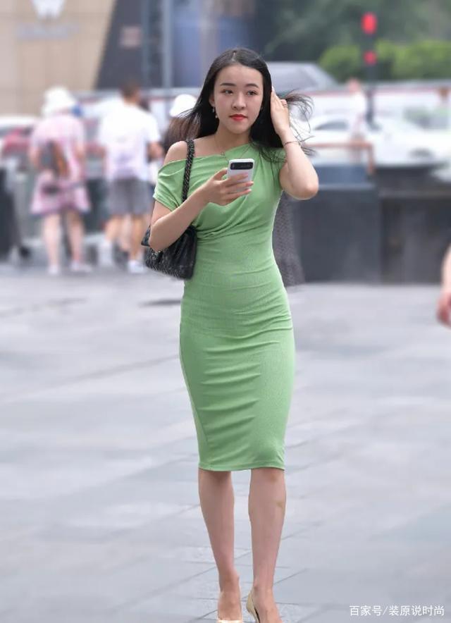 女孩很迷人,穿著綠色長裙顯得時尚優雅,成為過客眼中的美麗風景