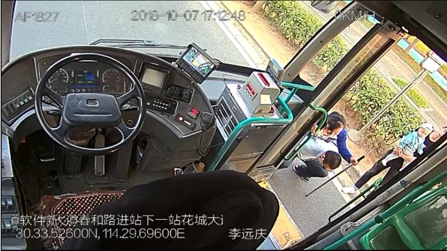 看到残疾女乘客要上车,公交司机弯腰蹲下,把她背到座位上